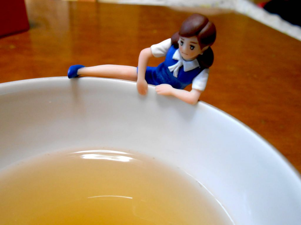 Fuchico in a blue uniform on the edge of a cup