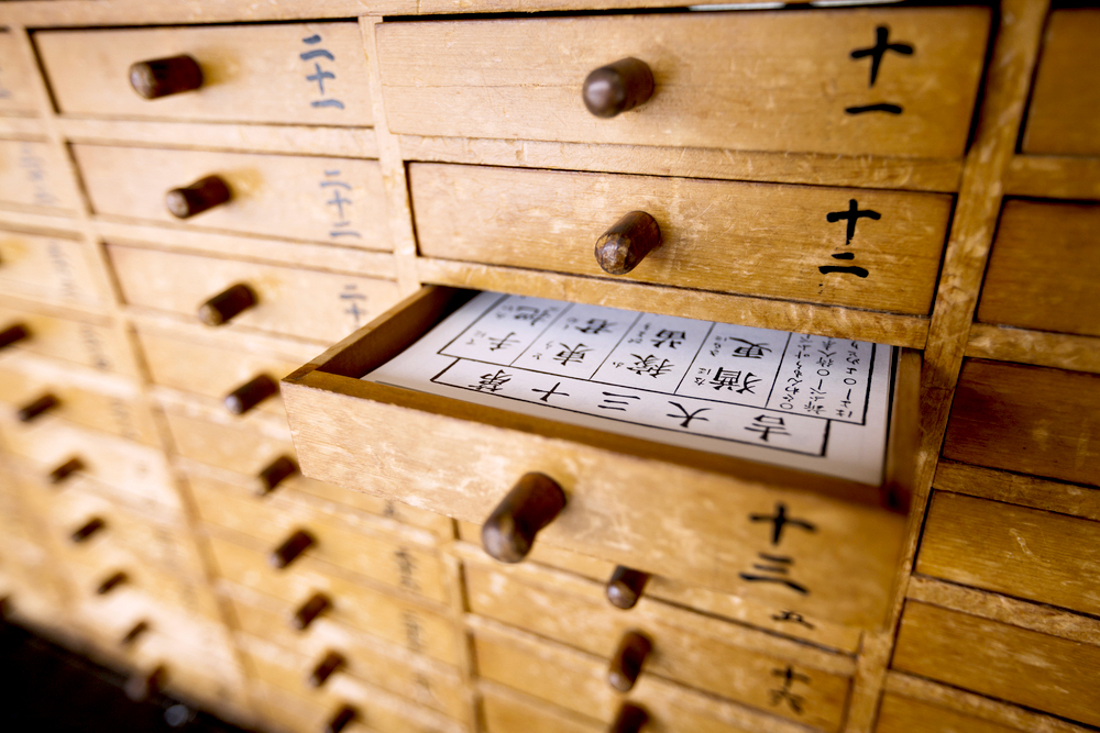 Omikuji at Shinto Shrine, a drawer opend with a fortune slip in it out of many other drawers