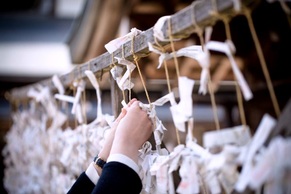A Japanese fortune slip being tied to a rope at a shrine