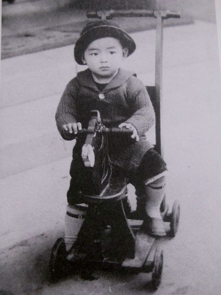 Mizuki Shigeru at the age 3 riding on a tricycle