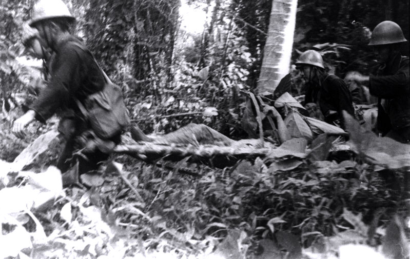 Soldiers carrying an injured one in the jungle of Rabaul in the island of New Britain 1944