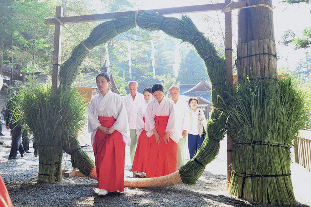 Shinto ritual, Nagoshi-no-Harae, Summer purification , Shinto female shaman, Miko ig going through the huge ring to purify the impurity