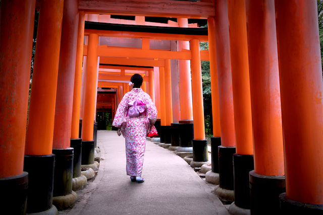 A woman in kimono walks under the torii gates of Fusimi Inari Shrine in Kyoto