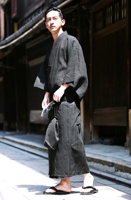 A Man in Charcoal Gray Japanese Traditional Casual Dress holding a fan and a purse
