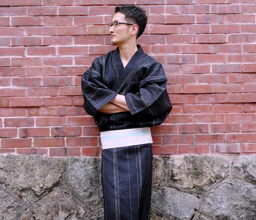 A man in charcoal gray Japanese Traditional Casual Dress with glasses in front of the brick wall